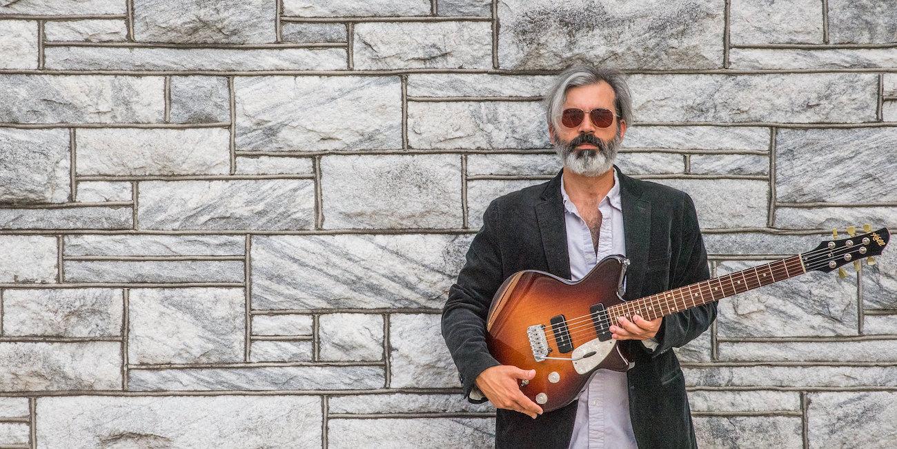 Kitaristi Mike Baggetta seisoo intrumenttinsa kädessään.