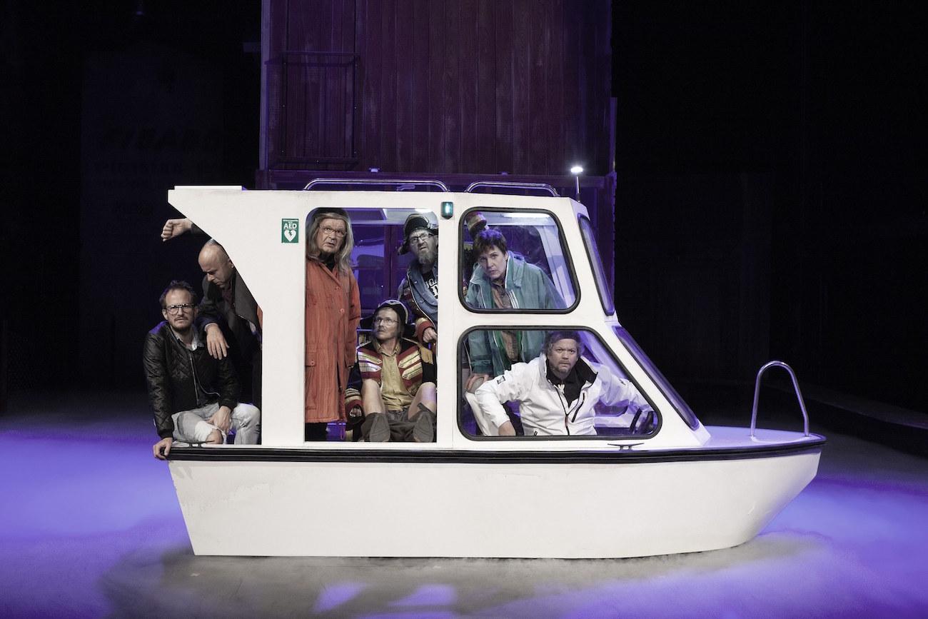 Arktiset leikit -näytelmän näyttelijät sulloutuneena näyttämöllä olevaan veneeseen.
