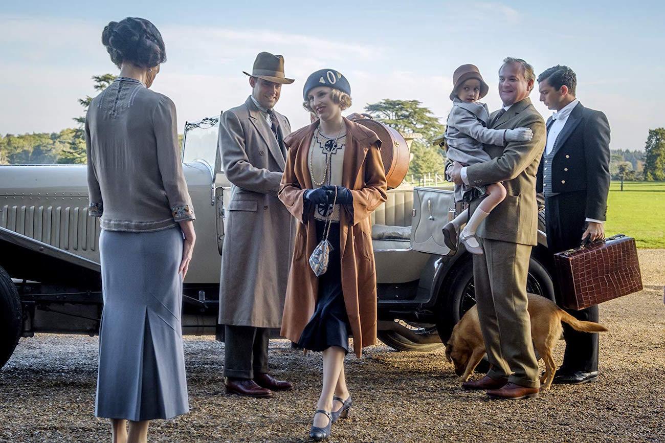 Elizabeth McGovern, Harry Hadden-Paton, Laura Carmichael ja Hugh Bonneville tervehtivät henkilöauton edessä Downton Abbey -elokuvassa.