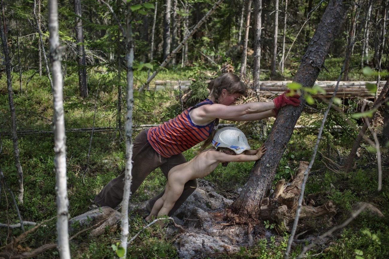 Touko Hujasen valokuva, jossa Maria Dorff kaataa lapsensa kanssa puuta.