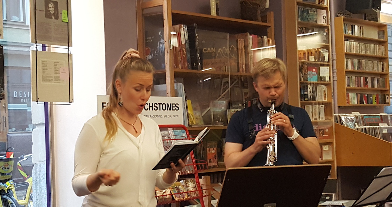 Mikko Innanen soittaa ja Outi-Illuusia Parviainen lausuu maakuntalauluja helsinkiläisessä Digelius-levykaupassa.