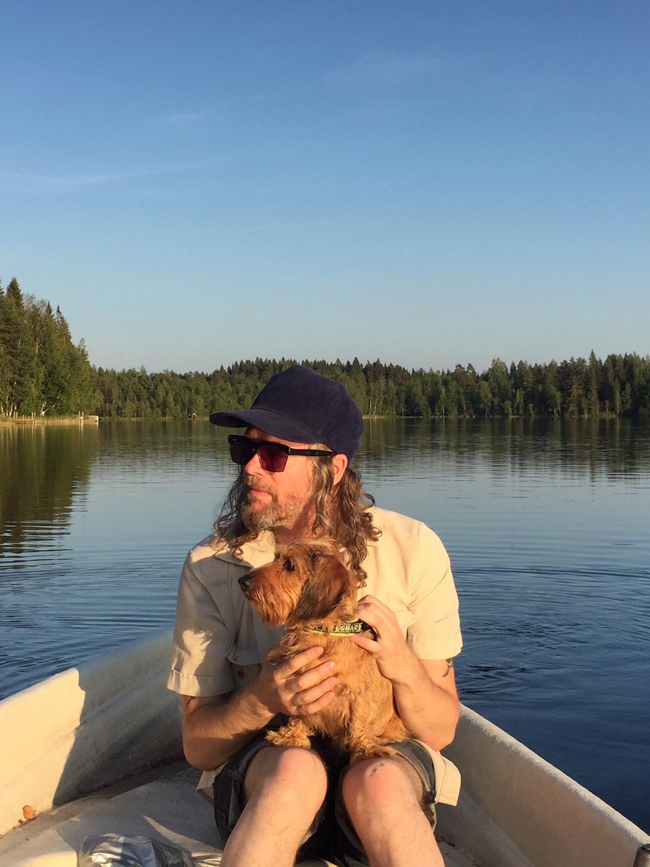 Ville Pirinen ja koira soutuveneessä.
